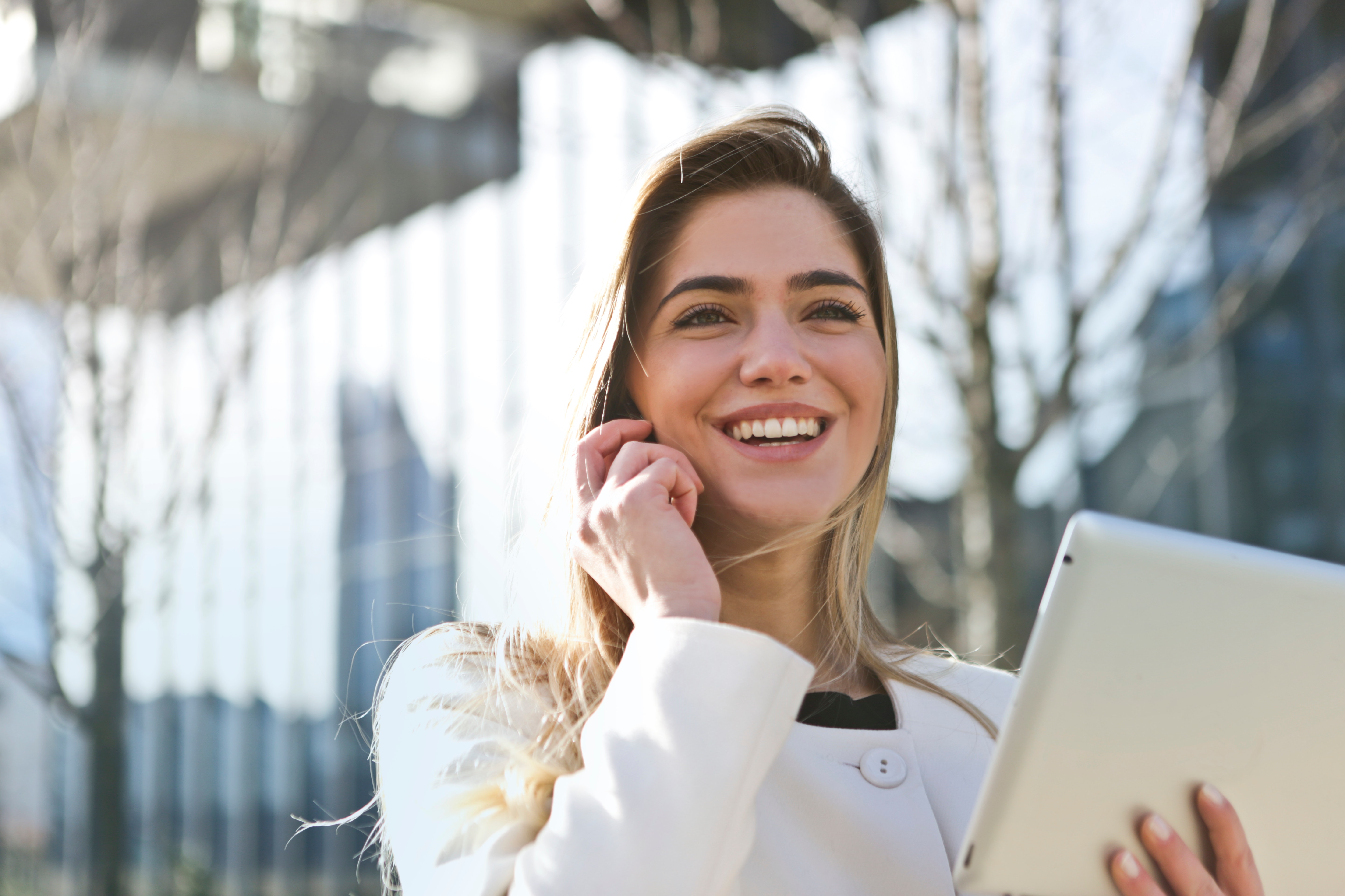 young woman smiling with ipad